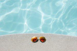 occhiali da sole su bordo piscina
